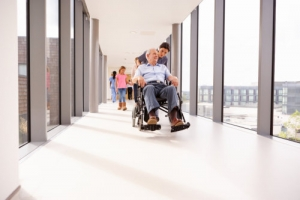 caregiver assisting elderly man in a wheelchair