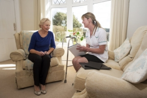 caregiver on a home visit talking with an senior woman patient