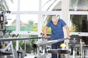 senior man taking support of bars while walking in fitness studio
